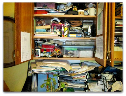 cluttered cupboard with paperwork spilling everywhere