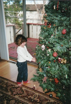 little girl putting ornaments on a Christmas tree