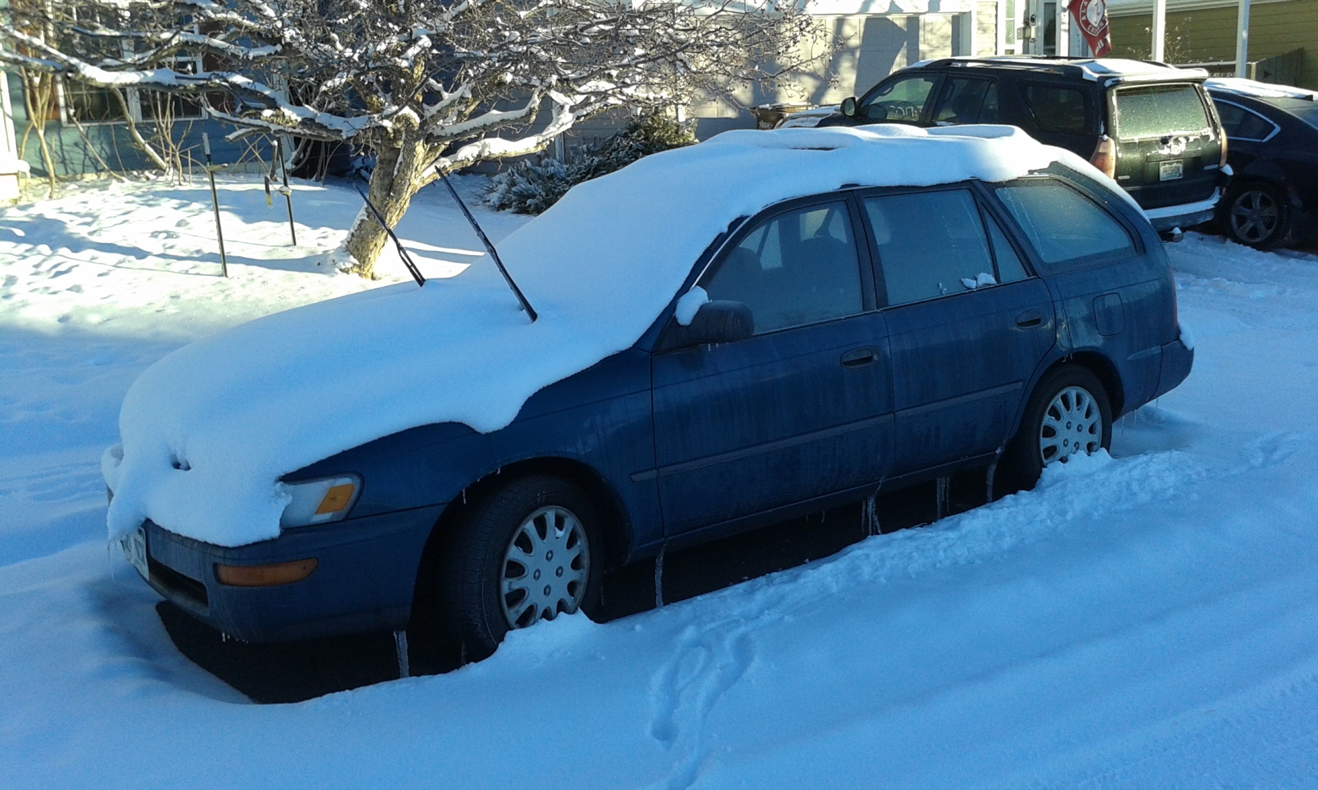 car buried in the snow at the curb