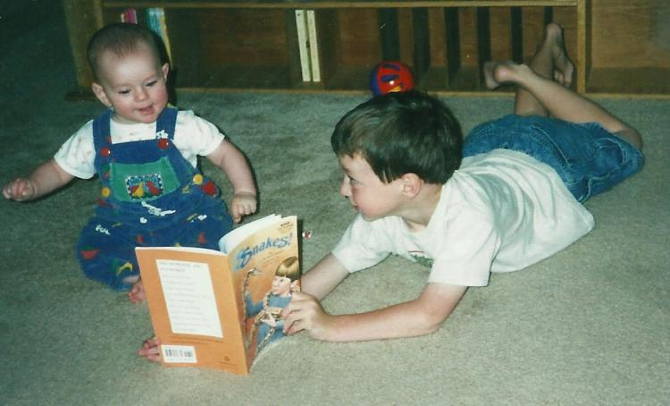 five year old boy reading to one year old girl